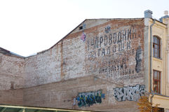Old wall with graffiti. Wall of old house with old advertising and modern graffiti Royalty Free Stock Photo