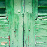 in the old wall a hinged window green wood and rusty metal Stock Image