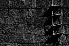 Old Wall with Ladder. Dark Wall Built of Rough Stones with Ladder in a Harbour Stock Images