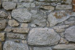 Old wall made of big stones and broken bricks. Vintage rough blocks surface background royalty free stock image