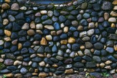 A wall made of round rocks stock images