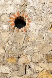 Old wall with a circular small window - Liguria Italy. Old wall made of stones, bricks and concrete with a circular small window. Liguria, Italy, Europe stock photos