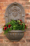 Old wall mounted pot. With flowers Royalty Free Stock Photo