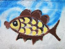Old wall with painted fish, Lithuania. Old white wall with painted colorful fish stock images