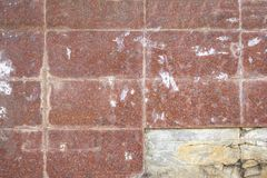 Old wall of rectangular red tiles with stains of paint and dirt and broken tile. rough surface texture. A old wall of rectangular red tiles with stains of paint royalty free stock photos