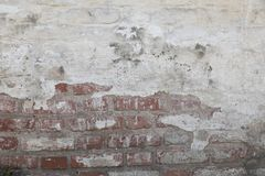 Old wall from a white brick with a regular layin. Horizontal direct. Old wall from a red brick plastered from above and covered with white paint. Plaster in royalty free stock photos