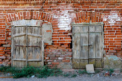Old wall of red brick with two closed windows Stock Image
