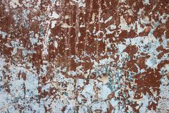 Old wall with shabby plaster. A dilapidated surface with peeling plaster. Brown, blue and white colors. Requires repair, finishing work. Daylight Royalty Free Stock Images