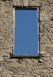 Old wall with sky through window. An old abandoned building with blue sky showing through window Royalty Free Stock Photo