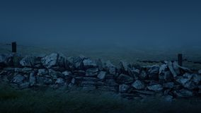 Old Wall In Storm With Mist Rushing Past At Night. Weathered old stone wall with barbed wire in stormy weather stock footage
