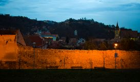The old wall that surrounds the old Brasov City. Black Church in the background. Blue hour image. stock photos