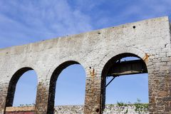 Old wall with three open archways that once held windows, abandoned building ruins. Horizontal aspect stock photo