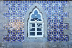 Old wall with traditional Portuguese decor tiles azulezhu in blue,yellow and brown tones with an old window as background. Old wall with traditional Portuguese stock photos