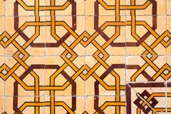 Old wall with traditional Portuguese decor tiles azulezhu in yellow and brown tones on a beige background. Old wall with traditional Portuguese decor tiles royalty free stock photography