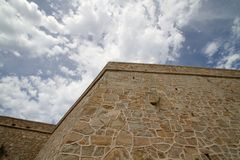 Old wall under a cloudy sky. Old stones wall under a cloudy sky Royalty Free Stock Photos