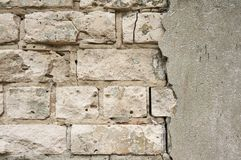 The old wall of white brick with a broken, cracked plaster. Abstract background. stock photos
