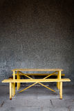 Old wall and yellow table with a bench Royalty Free Stock Images