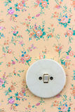 Old wallpaper with light switch Stock Photo