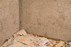Old wallpaper removing during repairs background . Concrete wall with wallpaper scraps on the floor . Stock Photography