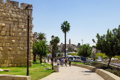 Old walls of Jerusalem with people entering Jaffa gate Stock Photos