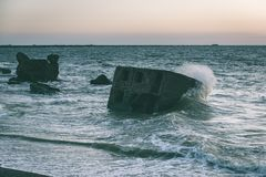 Old war fort ruins on the beach - vintage green look. Old war fort ruins on the beach with high waves in sunset. Liepaja, Latvia - vintage green look Royalty Free Stock Images