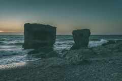 Old war fort ruins on the beach - vintage green look. Old war fort ruins on the beach with high waves in sunset. Liepaja, Latvia - vintage green look Royalty Free Stock Photo