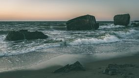 Old war fort ruins on the beach - vintage green look. Old war fort ruins on the beach with high waves in sunset. Liepaja, Latvia - vintage green look Stock Images