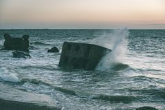Old war fort ruins on the beach - vintage green look. Old war fort ruins on the beach with high waves in sunset. Liepaja, Latvia - vintage green look Stock Photography