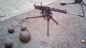 Old war guns and cannon balls. Metal old cannon balls from antique and modern automatic rifle Stock Images