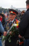 Old war veteran with flowers, Victory Day. MOSCOW, RUSSIA - MAY 09: Victory Day celebration on Poklonnaya Hill (Moscow) on May 09, 2012 in Moscow, Russia Royalty Free Stock Image