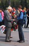 Old war veteran taking flowers from a boy Stock Photos