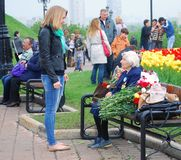 Old war veteran talking to a young girl. Senior war veteran woman sitting on a bench talking to a young girl standing in front of her. Victory Day celebration on Royalty Free Stock Image