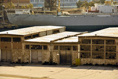 Old warehouse building. Shot of an old warehouse building and a cargo vessel at the background Stock Photography