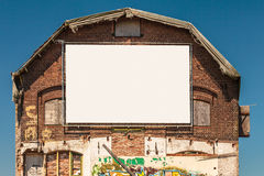 Old warehouse with an empty blank white canvas billboard Stock Image