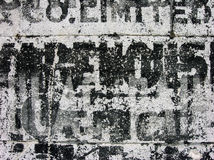 Old warehouse stencils on concrete. A close-up shot of weathered stencils painted onto a concrete wall royalty free stock photos