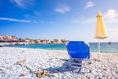 Old warehouses in the small port of Gerolimenas village, Mani region, Lakonia, Peloponnese. Seat and umbrella on the beach in the small port of Gerolimenas stock images