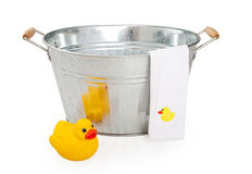 Old wash tub with rubber duck. Old galvanized wash tub with yellow rubber duck and towel Stock Photo
