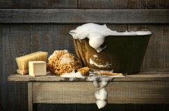 Old wash tub with soap on bench. Old wash tub with soap on rustic bench stock photography