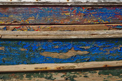 Old and washed out boat hull. Old and washed out fishing boat hull. Several layers of paint peeling off the wooden surface Stock Image