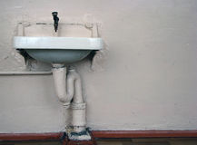 Old washstand. Old broken sink against the beige walls dirty Royalty Free Stock Photography
