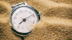 Old watch buried in sand Stock Image