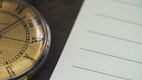 Old watch lies on the table near a blank notebook paper. Old watch lies on the table near a blank notebook paper stock video footage