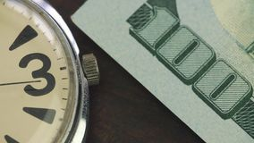 Old watch lies on the table on onde hundred dollar banknote.  stock video footage