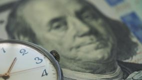 Old watch lies on the table on onde hundred dollar banknote.  stock video