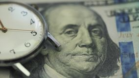 Old watch lies on the table on onde hundred dollar banknote.  stock footage