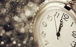 Old watch pointing midnight - New Year concept. New Year's at midnight - Old watch with stars, snowflakes and holiday lights royalty free stock photo