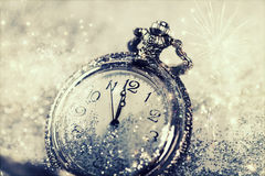 Old watch pointing midnight - New Year concept. New Year's at midnight - Old watch with stars, snowflakes and holiday lights royalty free stock photography