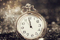 Old watch pointing midnight - New Year concept. New Year's at midnight - Old watch with stars, snowflakes and holiday lights stock photos