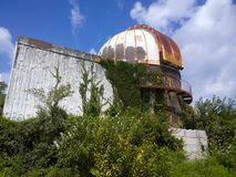 Old Watcher. Abandoned observatory overrun by advancing vegetation under the clouds and blue sky stock photography