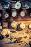 Old watchmaker's workshop with clocks to repair. Closeup of old watchmaker's workshop with clocks to repair stock photos